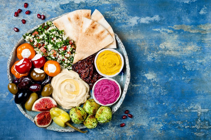 Mediterranean breads, dips, and peppers on a plate.