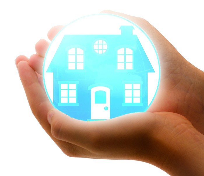 Hands holding a bubble with a glowing house inside it