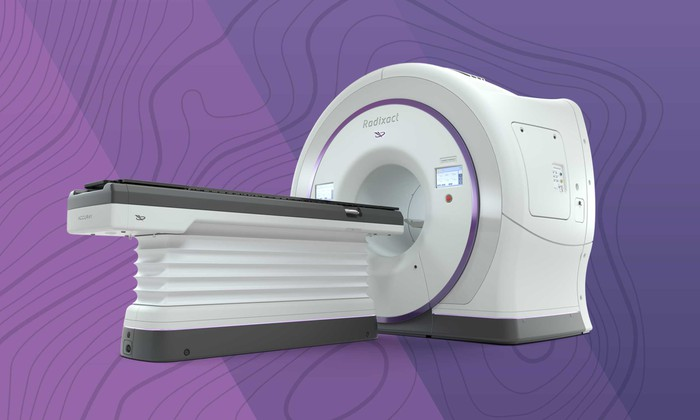 White machine with flat surface for a person to lie and a hole for scans of a patient's head.