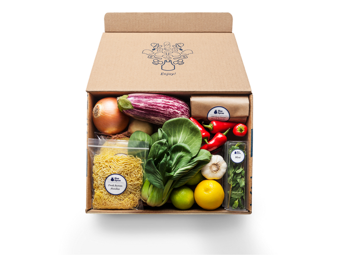 A box of ingredients from Blue Apron, including several vegetables and noodles