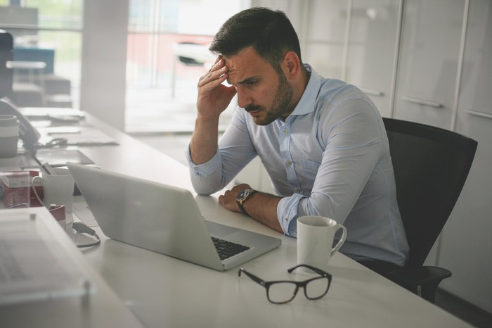 Head in hand, a troubled businessman stares at a computer screen.