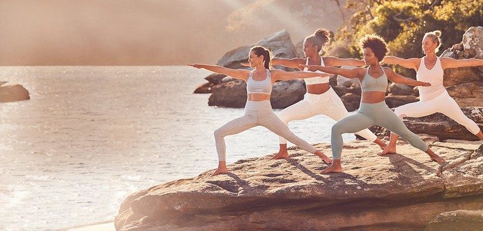 Four women in Athleta apparel striking the same yoga pose on a large rock