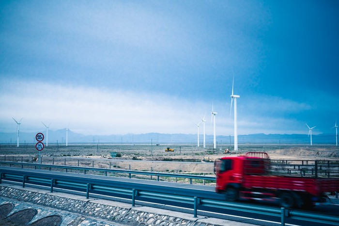 Wind turbines in a field with a red truck on a highway passing in front.