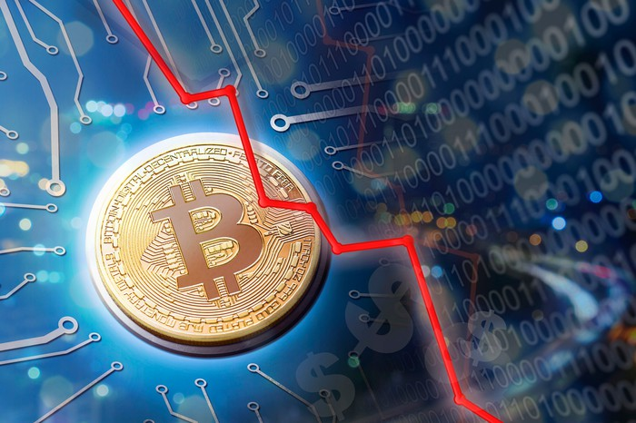 A declining red line overlaid on a physical gold bitcoin, surrounded by binary code and circuitry.