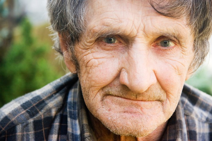 An elderly man in a flannel shirt pensively smirking.