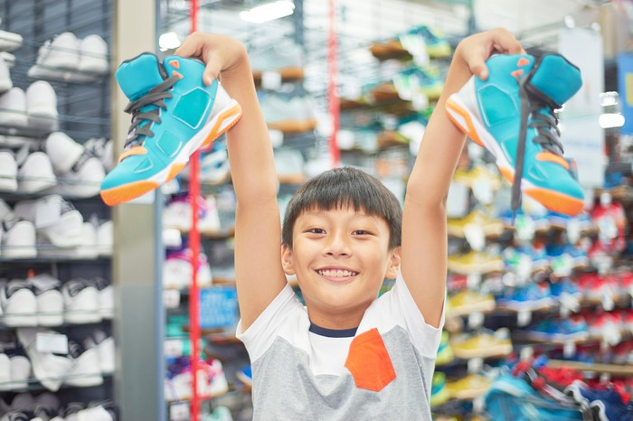 A young boy holds up a pair of sneakers.