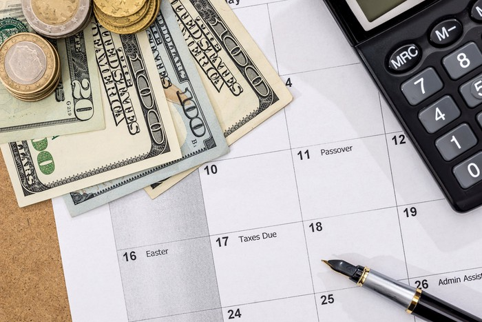 A calendar with dollars, coins, a pen and a calculator on it.