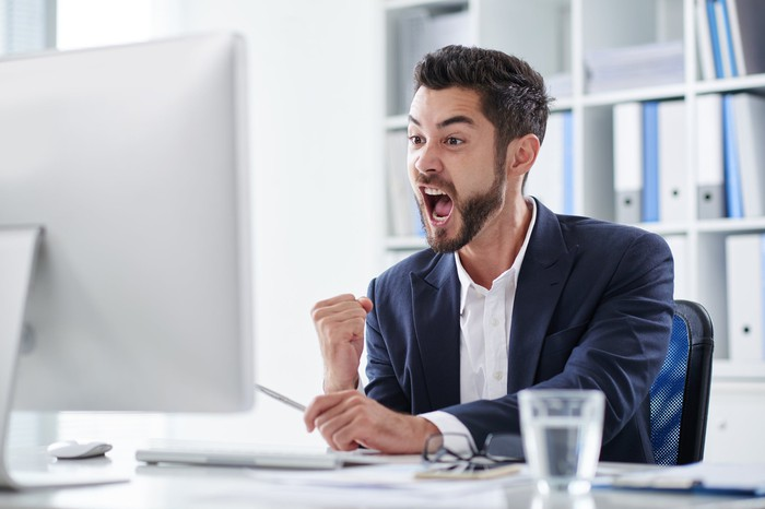 Happy young man screaming of joy when looking at computer screen