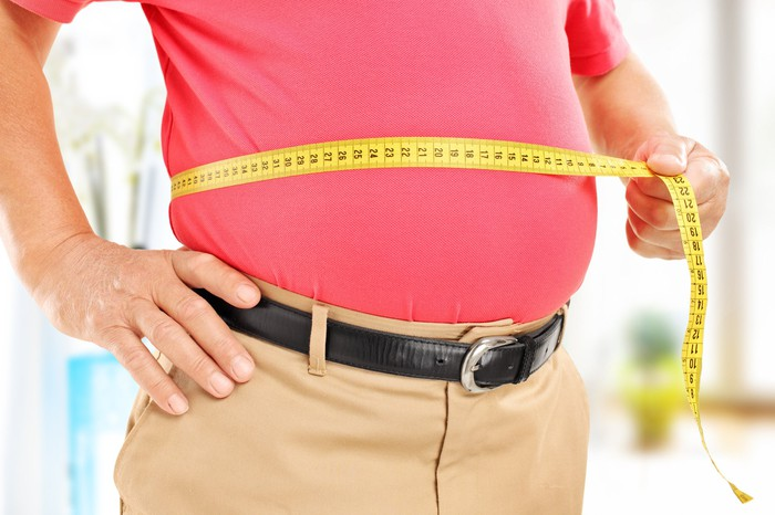 A man holding a tape measure around his stomach.