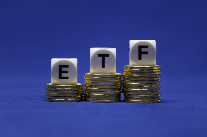 Three rising stacks of gold coins with dice spelling ETF on top of them