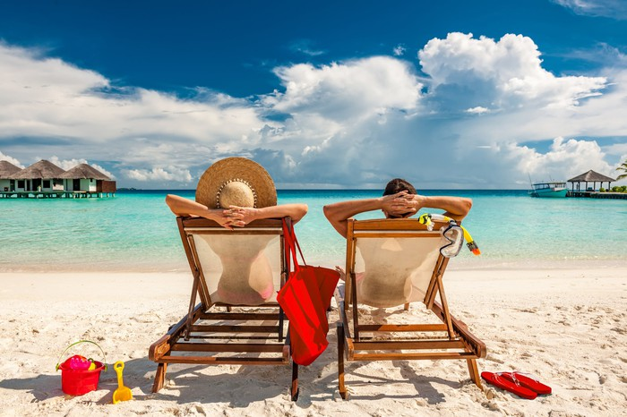 Two people in recliners on a beach with their hands behind their heads. The sky is blue, the water is clear, and there are some clouds and sand.