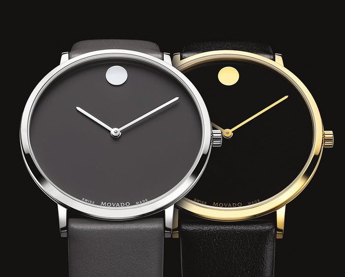 Two Movado watches with clean black face, black bands, and gold and silver trim.