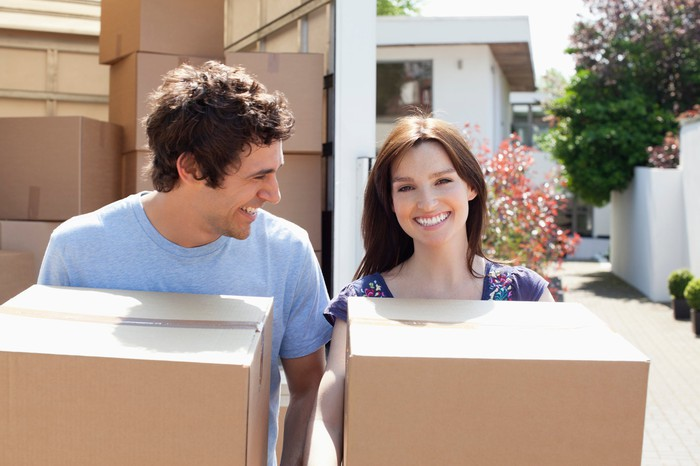 A young adult male and female carrying boxes from a truck parked in front of a home.