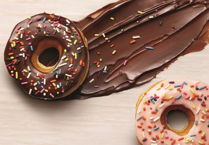 Two doughnuts with colorful sprinkles on wood table.