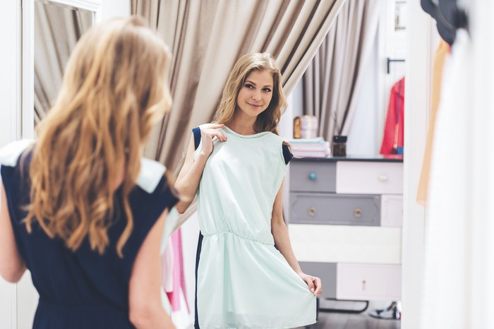 A person holding up a dress in front of a mirror to see if it will fit.