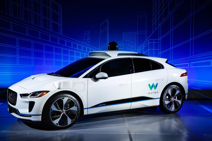 A white Jaguar I-Pace with Waymo markings and visible self-driving sensor hardware.