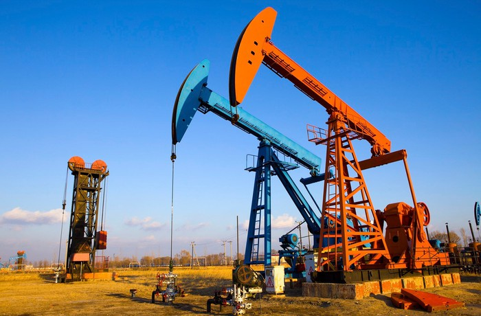Two oil pump jacks and a gas pump in operation.