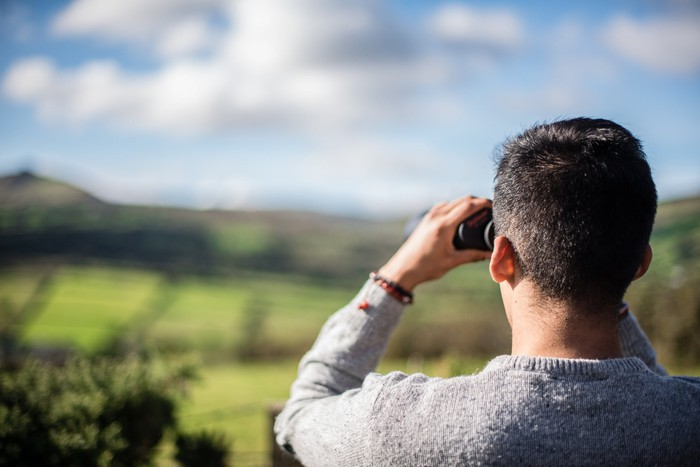 Man with binoculars looking off into the distance