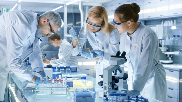 Four scientists in lab performing research