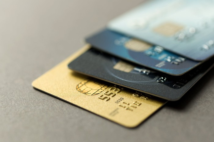 Four credit cards on a flat grey surface.