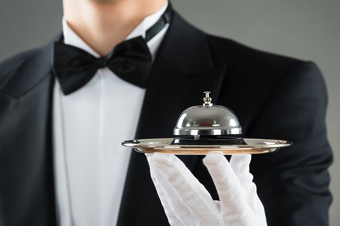 White-gloved waiter holding service bell on plate