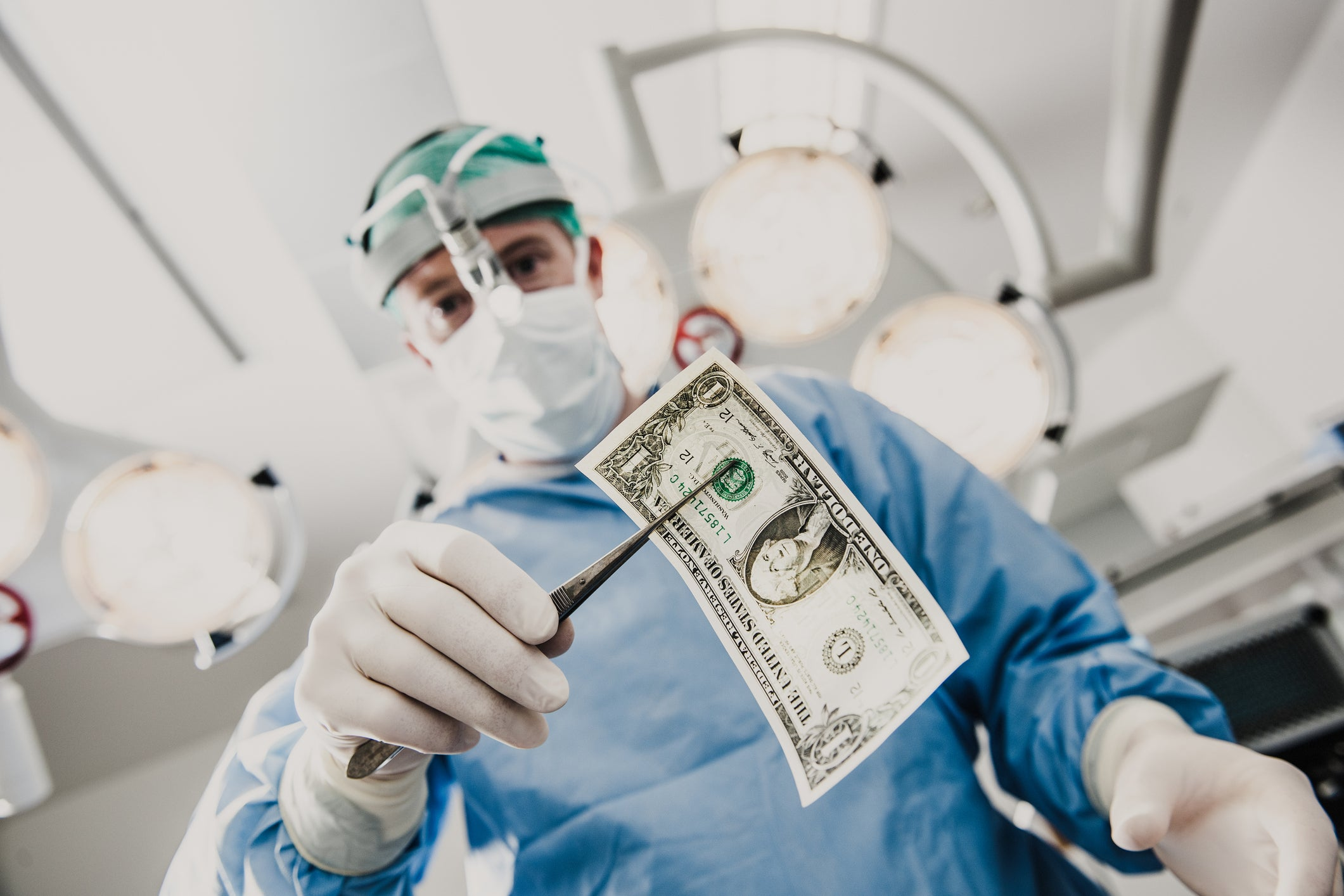 Surgeon holding dollar bill with forceps.