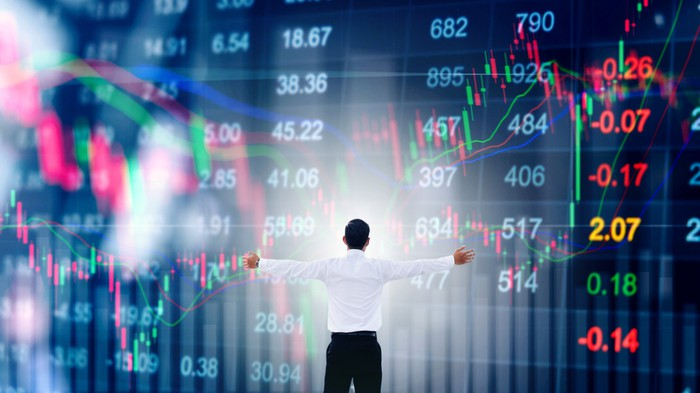Man with arms outstretched in front of large display showing stock data and stock chart going up