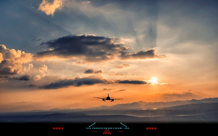 Airplane flying into setting sun