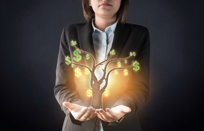 A businesswoman with hands outstretched and holding a graphic of a tree with green dollar signs hanging from it.