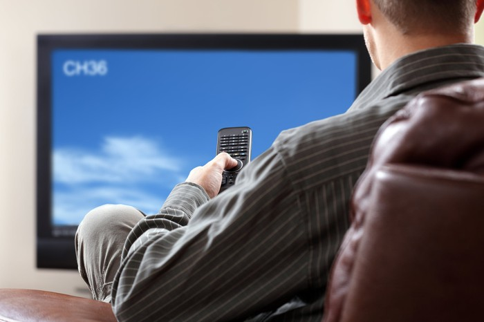 An over-the-shoulder view of a person sitting in a chair, remot in had, watching TV.