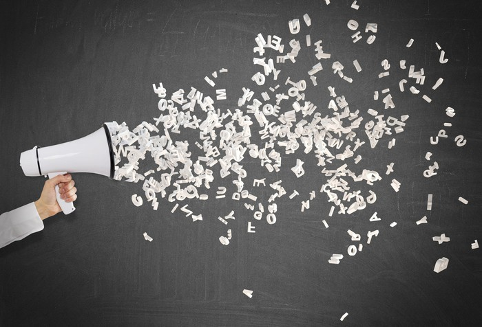 Letters shooting out of a megaphone held in someone's hand.