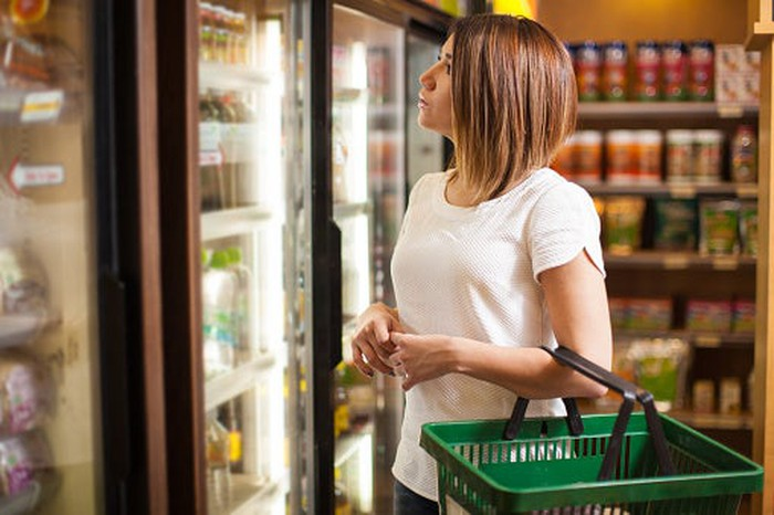 Shopper looking over items in refrigerated cooler.