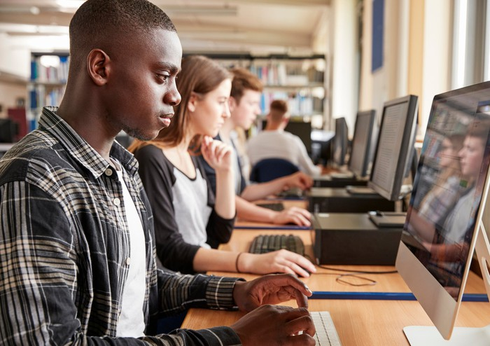 College-age people use computers in a library.