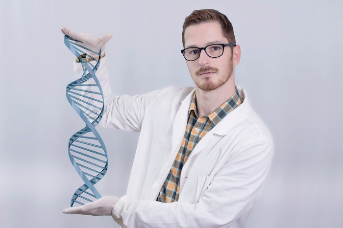A biotech lab researcher holding a DNA double helix model in his hands.