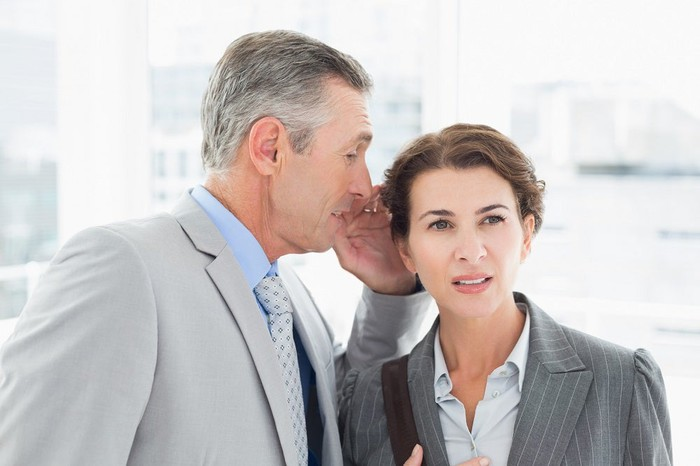 A businessman whispers into a businesswoman's ear.