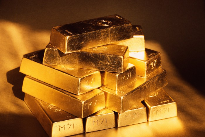A pile of gold bars stacked four-high.