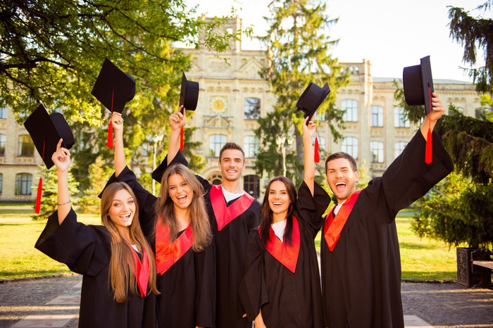 Group of young adults in graduation gowns holding up caps
