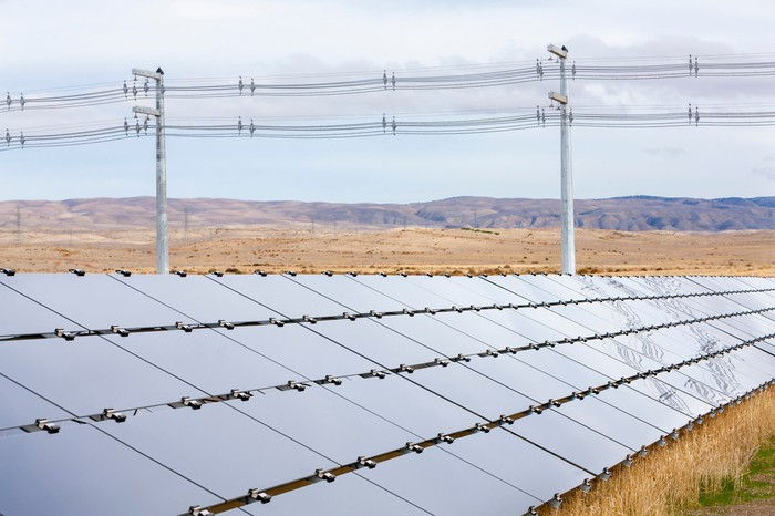 Rows of solar panels on ground-mounts in front of transmission lines in an arid, hilly area.