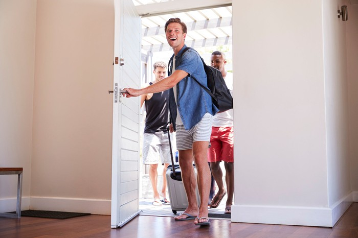 Three people in shorts and t-shirts enter the front door of a home carrying luggage.