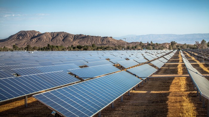 Solar farm in a desert with mountains in the background.