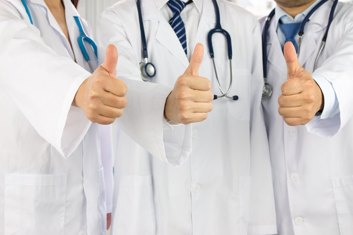 Three doctors giving a thumbs up signal.