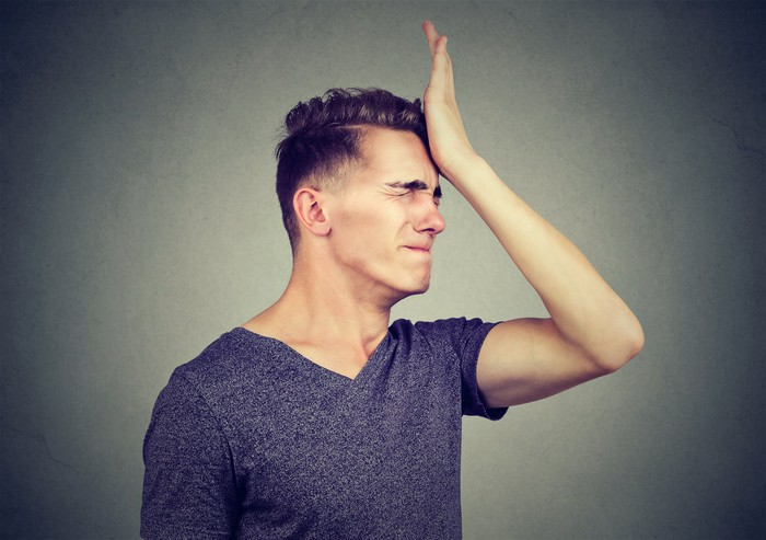 Man smacking his forehead with his palm.