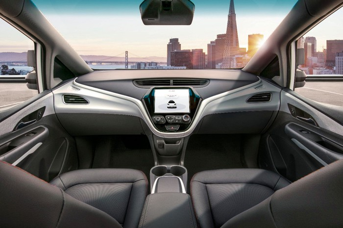 A view of the GM Cruise's front seats and dashboard. The vehicle has no steering wheel or pedals.