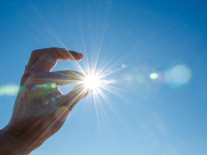 Fingers appearing to pinch the sun in the sky
