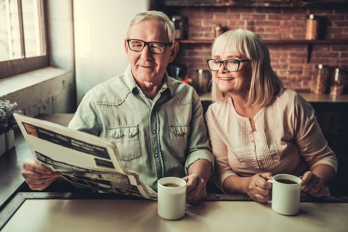 Senior couple sitting at a table with coffee mugs and sharing a newspaper