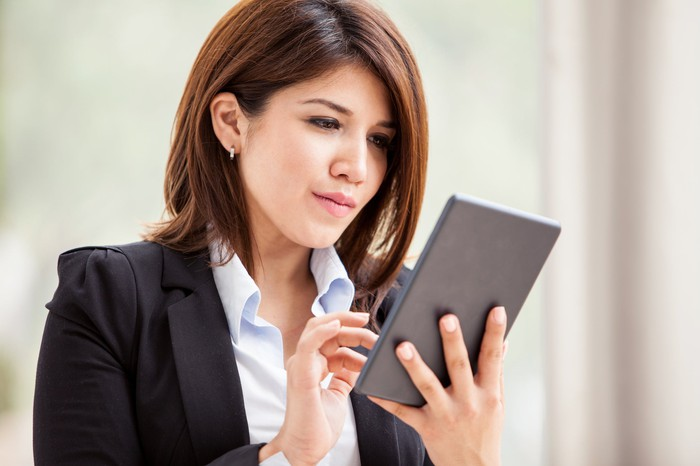 Young woman in a suit, focused on a tablet