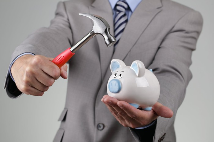Man in suit holding a hammer aimed toward a piggy bank