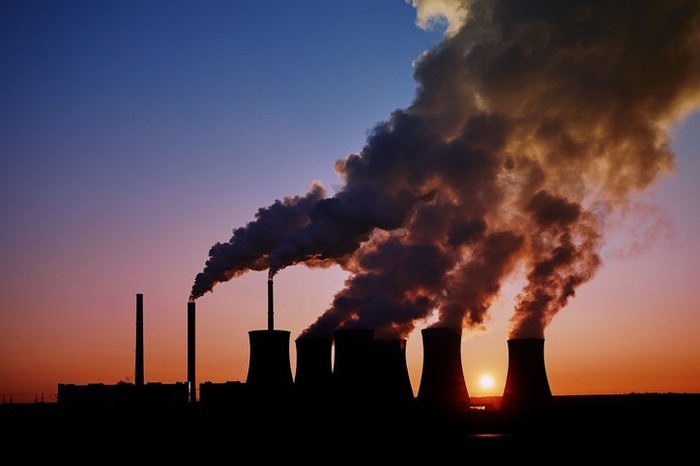 Steam rising from the cooling towers of a coal-fired power plant in silhouette.