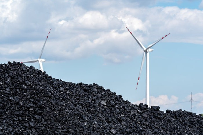 A pile of coal in the foreground, with several wind turbines in the background.