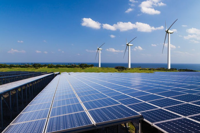 Solar panels in the forefront and large wind turbines in the background.